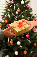 Close-up of two people's hands holding a Christmas present