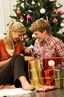 Mid adult man and a young woman looking at a Christmas present and smiling