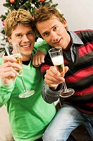 Portrait of two mid adult men holding champagne flutes and smiling