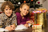 Portrait of a boy and girl lying near Christmas presents and smiling