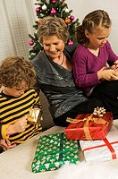 High angle view of a senior woman sitting with her grandson and granddaughter opening Christmas presents