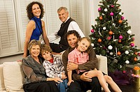 Portrait of a family sitting and smiling near a Christmas tree