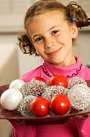 Portrait of a girl holding a tray of Christmas balls