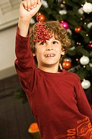 Close-up of a boy holding a Christmas ornament and smiling