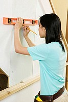 Side profile of a young woman using a spirit level to mark on a wall