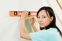 Portrait of a young woman using spirit level to mark on a wall
