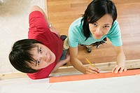 High angle view of a young woman using a spirit level to mark on a wall with a young man standing beside her