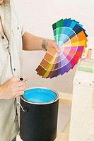 Mid section view of a man holding color swatches and a paint can (thumbnail)