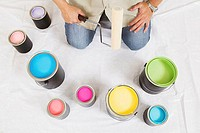 High angle view of a man holding a paint roller with paint cans in front of him