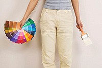 Mid section view of a woman holding color swatches and a paintbrush