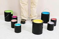 Low section view of a woman standing with paint cans around him