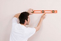 Rear view of a young man using a spirit level to mark on a wall