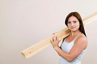 Portrait of a young woman carrying planks on her shoulders