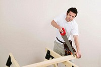 Portrait of a young man cutting a plank with a saw