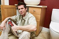 Portrait of a young man holding an adjustable wrench in the bathroom