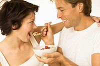 Close-up of a young man feeding a young woman (thumbnail)