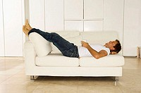 Side profile of a young man lying on a couch