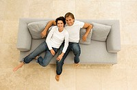 Portrait of a young couple sitting on a couch and smiling