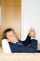 Portrait of a businessman sitting in an armchair and holding a mobile phone (thumbnail)