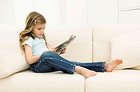 Girl reading a magazine on a couch