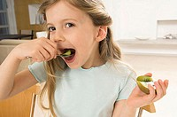 Portrait of a girl eating a kiwi