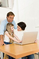 Girl using a laptop with her parents