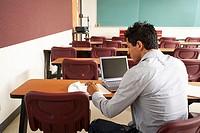 Rear view of a college student sitting in a lecture hall in front of a laptop