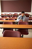 College student sitting in a lecture hall and using a laptop (thumbnail)