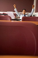 College student sitting in a lecture hall with his arms raised (thumbnail)