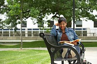 Portrait of a college student sitting on a bench and holding a book