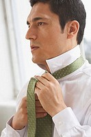 Side profile of a businessman tying his tie