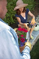 High angle view of a mature woman holding a potted plant and a mature man standing with a trowel (thumbnail)