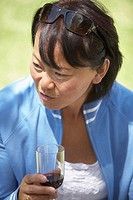 Close-up of a mature woman holding a glass of red wine