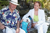 Close-up of a mature couple sitting in a garden with a dog in a bag