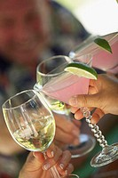 Close-up of three people's hands toasting with glasses