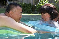 Close-up of a mature couple lying on a pool raft in a swimming pool
