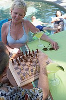 High angle view of a mature couple playing chess at poolside