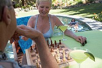 Close-up of a mature couple playing chess at poolside