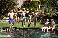 Group of people holding each other's hand and jumping into a swimming pool