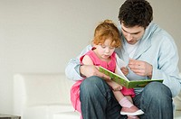 Father and daughter reading at home
