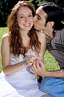 Young man kissing young woman in garden, close-up