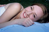 Young woman lying on chest of man, smiling, close-up