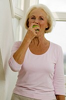 Senior woman eating fruit, portrait