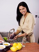 Woman washing grapes at kitchen sink, smiling