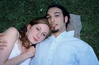 Young couple lying on grass, portrait, close-up