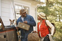 Middle-aged African American couple carrying fishing equipment