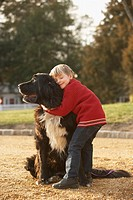 Young boy hugging dog outdoors