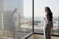 Hispanic businesswoman looking out a window, Los Angeles, California, United States