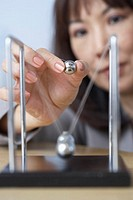 Close up of businesswoman starting perpetual motion device