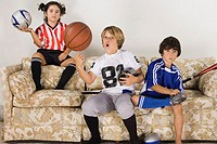 Group of children in sports gear on the sofa